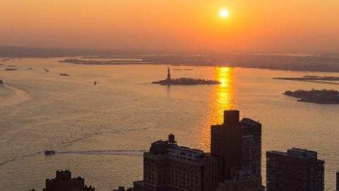 Image 1: View of Liberty Island at sundown from 140 Broadway